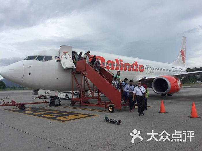 飞机降落机场后,吉隆坡正下着大雨,乘客从飞机悬梯下来到摆渡车却是